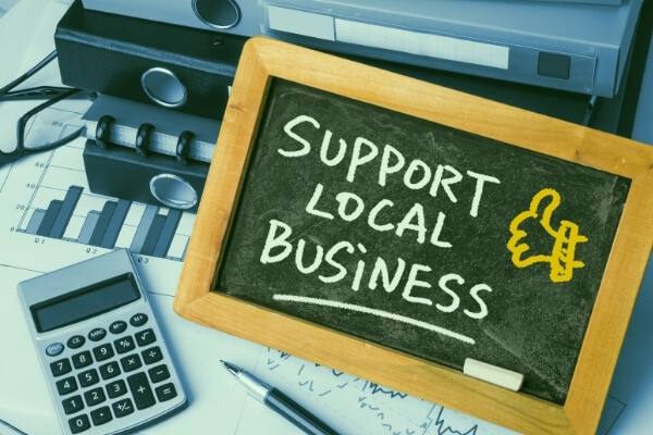 "Small chalkboard that reads ""Support Local Business"" sitting on top of office supplies"