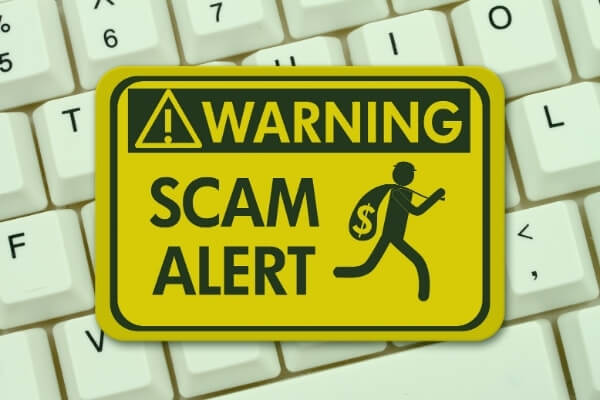 """Sign reading """"Warning: Scam Alert"""" on top of a keyboard"""