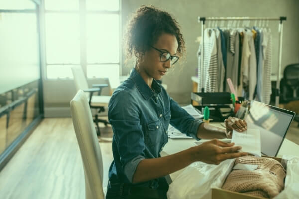 Young woman sitting at a desk filling a clothing order