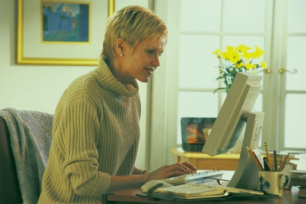 Middle aged woman sitting in front of a desktop computer