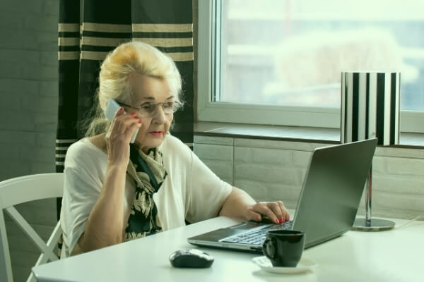Elderly woman talking on phone while using a laptop