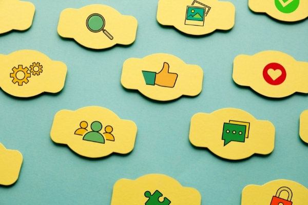 Variety of social media icons on yellow, cloud shaped cut outs
